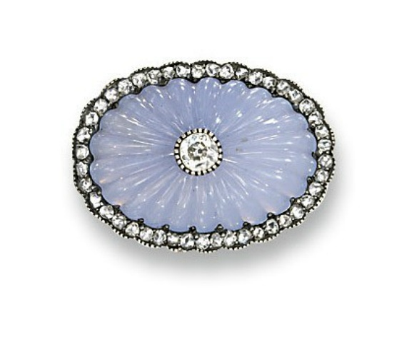 A RUSSIAN CHALCEDONY AND DIAMOND BROOCH, BY FABERGE   The oval-shaped ribbed 'mecca stone' with old-cut diamond collet centre to the rose-cut diamond border, circa 1895, 2.3 cm wide  With workmaster's mark for August Wilhelm Holmström, scratched inventory number 73792