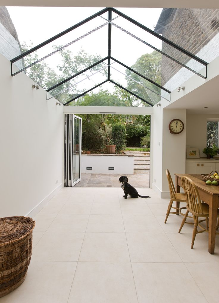 Side infill dining room extension with a frameless glass roof and glass beams