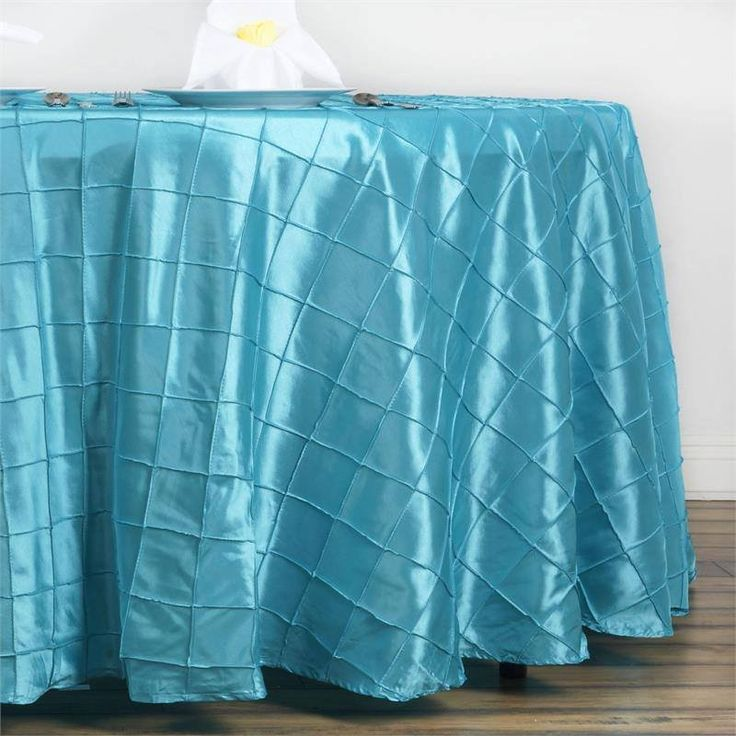 """Turquoise Pintuck Tablecloths 132"""" Round - Pintuck is actually a fold of fabric that is stitched intricately to hold it in a place, very much like a pleat. These lovely pleats impart a decorative effect to the fabric by fashioning a visual line at a chosen point. They effortlessly bridge vintage and contemporary styles to create a majestic new classic look. If you do not want your celebration to blend in with other weddings, birthdays, and anniversaries, try our premium quality pintuck…"""