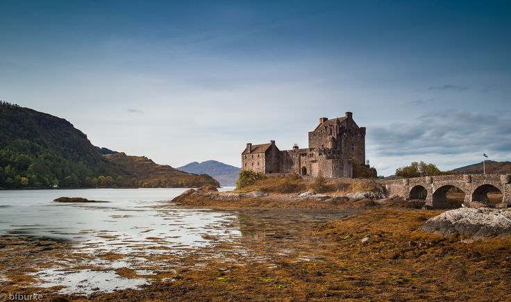 https://flic.kr/p/zEBBQ4   Eilean Donan Castle   Eilean Donan Castle looking fantastic on a clear autumns day.  This was a 13 second exposure to slightly smooth the water but also to minimise the impact of the tourists who were milling about on the castle and the bridge.   Upon first arriving I was wishing for a higher tide, but upon reflection (or not since the tide was out!) I actually like it this way with the burnt colours of the seaweed giving it that autumnal feeling.