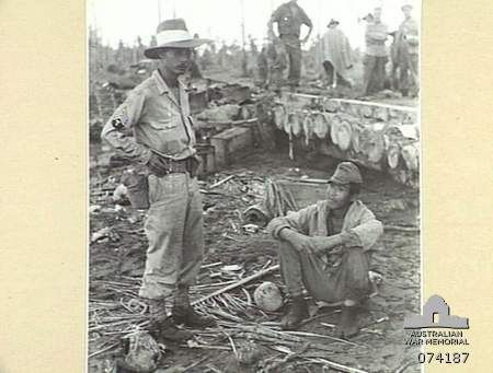 HANSA BAY, NEW GUINEA. 1944-06-21. SERGEANT J.H. IKUTA, ALLIED TRANSLATOR AND INTELLIGENCE SERVICE (1) INTERROGATING A JAPANESE SOLDIER CAPTURED BY MEMBERS OF THE PAPUAN INFANTRY BATTALION.