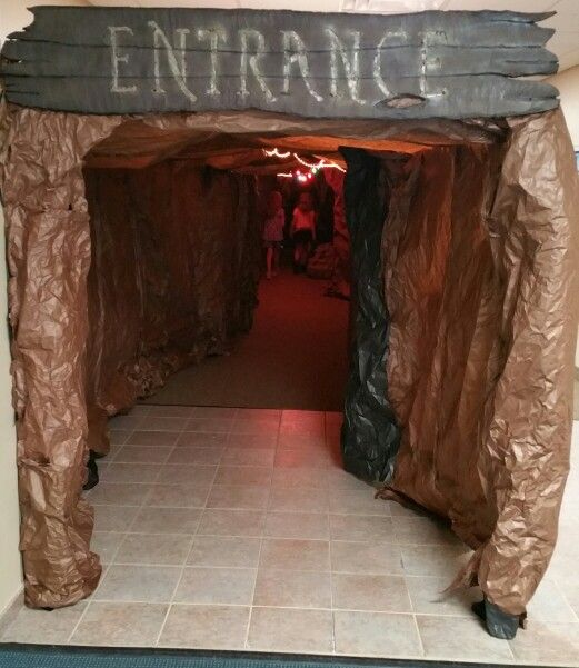 "Cave entrance, approximately 100ft. long, complete with a water feature. The kids had to go through it to get to the worship rally. Each day I added ""cave paintings"" for them to look for."