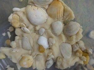White play dough and sea shells sensory tub.