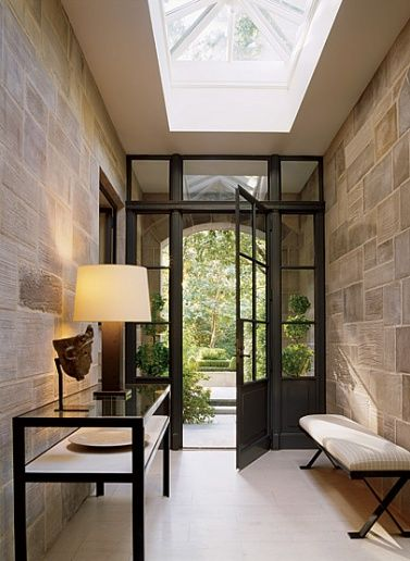 Nice use of a skylight; this small foyer seems so open. Love the stone walls and clean lines.