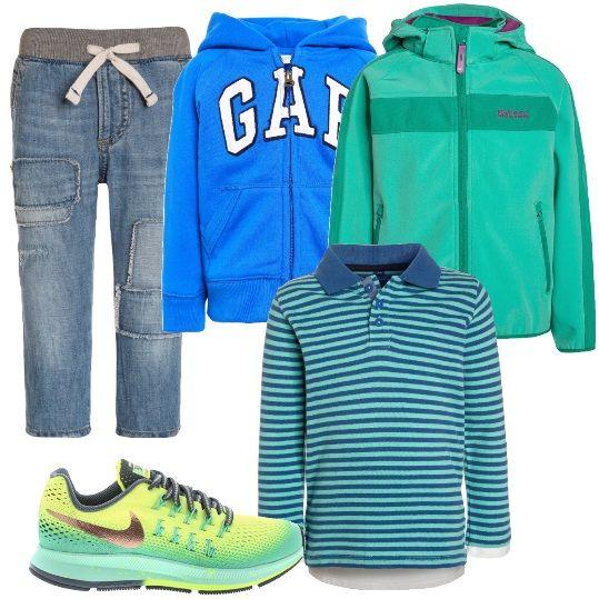 Per un bimbo comodo, allegro e frizzante: jeans baggy, con fascia in vita grigia e laccetti, polo a maniche lunghe a righe verdi e blu, felpa azzurra, con cappuccio, giacca color verde, traspirante, antivento, con cappuccio e sneakers colorate.