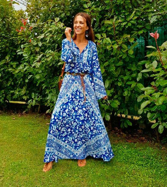 Paula Echevarria con un conjunto de falda larga y camisa que hacen el efecto de vestido largo, con el fondo azulón y flores blancas,de FETICHE SUANCES.
