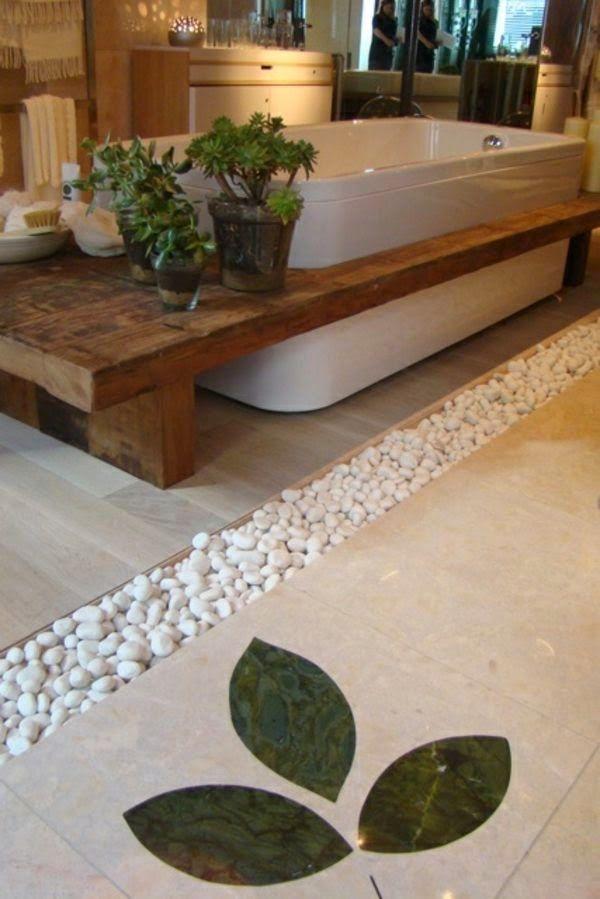 Baignoire moderne intégrée dans un plan en bois massif avec parquet et galets au sol.