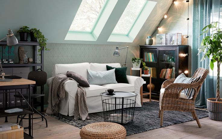 The traditional EKTORP 2-seat sofa in Vittaryd white sits opposite a BYHOLMA/MARIEBERG wicker chair in a small, cosy green, grey and white sitting room with a sloping roof.