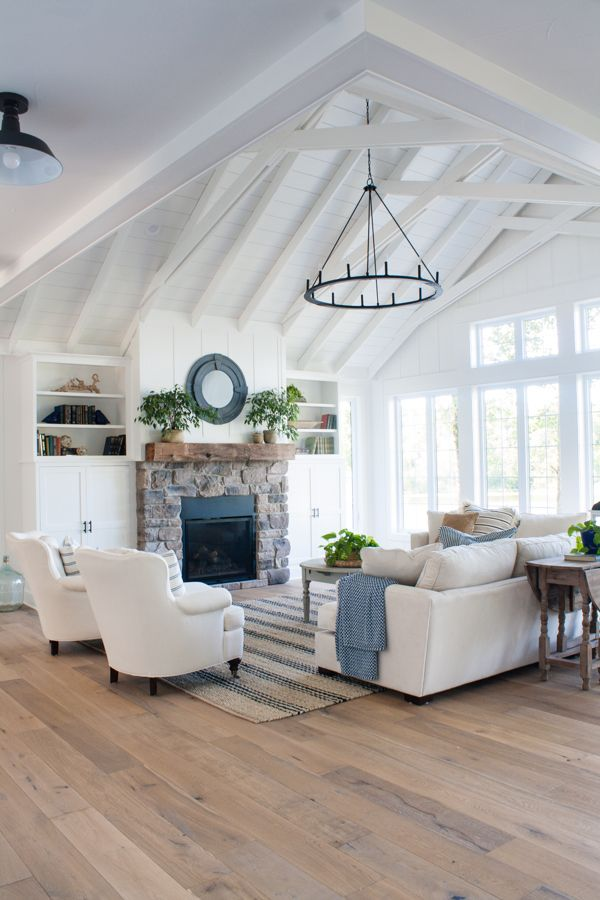 Lake House living room decor featuring white board and batten walls, a striped jute rug, comfy white couches and a rustic mantel.