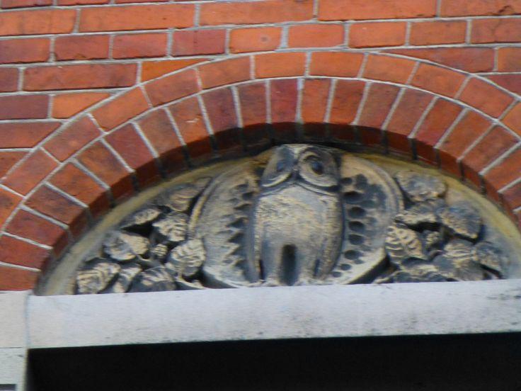 Et ugle-relief på facaden over Cafe Hack, Århus Teater. Uglen er attribut til gudinden Athene der er gudinde for bl.a. kunst.