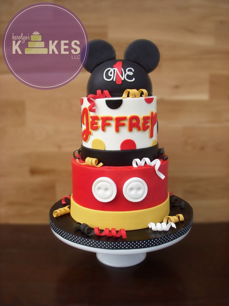 Mickey Mouse KAKE! Cake is iced in buttercream. Marshmallow Fondant buttons, name and curleys. Ears are rice cereal.