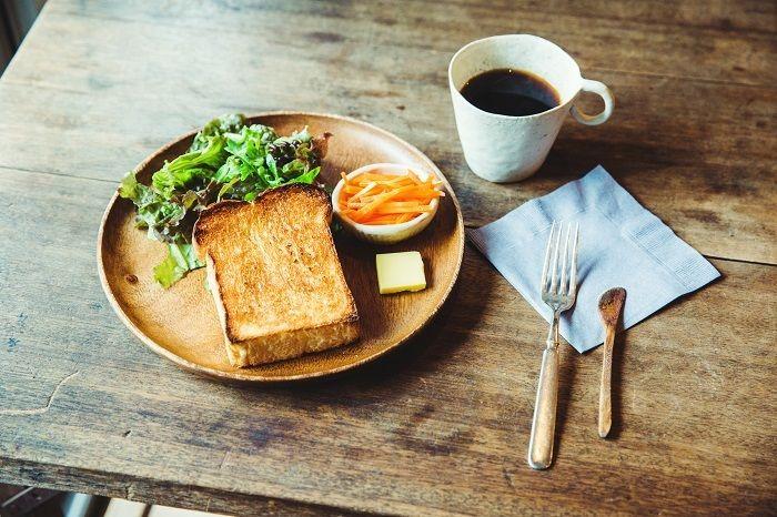 """食パン「まいにち」が主役のトーストのセット。一口かじるとサクサクっといい音とともに小麦の香りが広がります。手づくりの質感に温かみを感じるマグカップは、雑司が谷の「鬼子母神」と「大鳥神社」で開催される手創り市で一目惚れした「SŌK」のもの。作り手の鈴木絵里加さんとは""""えりかちゃん""""と呼ぶほどの仲良し"""