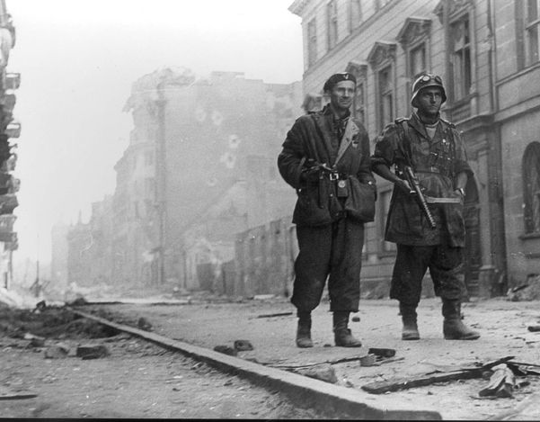 """Warsaw, Poland, Two Polish rebels, among them Walter Kostecki (right) in a ruined street during the Polish rebellion, 1944. The two rebels are dressed in German army uniform. They are also holding weapons taken from German soldiers who were killed. Walter Kostecki, A Catholic Polish man, was a member of the Polish underground, and assisted the rescue of Jews from Warsaw ghetto in Poland. He served in the Polish navy in exile."""""""