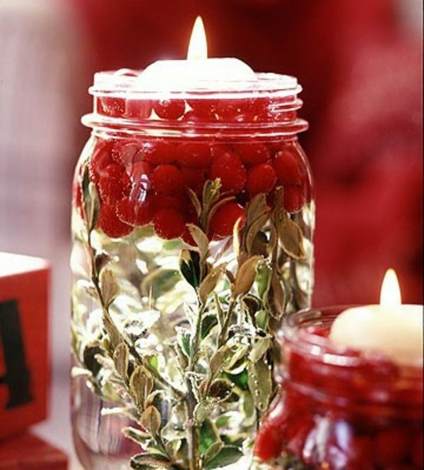 candle floaters in glass jar with cranberries and fresh herbs