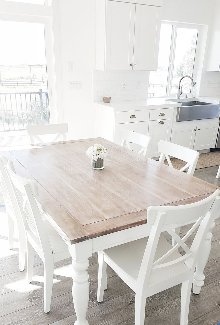#whitelanedecor @whitelanedecor Dining room table, liming wax table top, stainless steel farm sink, white cabinets with brass hardware, white x back Ikea chairs, white subway tile kitchen, farm sink, whitewashed table, Ikea INGOLF chairs, white table base with wood top.