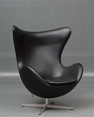 Arne Jacobsen (1902-1971). Ægget. Hvilestol model 3317 med  vippe funktion.Tilhørende skammel model 3127,  betrukket med sort classic læder, begge med fod af aluminium. Begge fremstillet hos Fritz Hansen. Formgivet i 1958-59 som en del af totalindretningen i Hotel Royal København. Litteratur: C Thau / K. Vindum 'Arne Jacobsen' 1998 Bl.a omtalt s. 144, 432 gengivet s. 433, 438-439, 467, 471-472.<br> Fremstår med let patinering og enkelte ridser.  (2)
