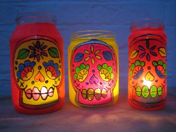 fabulously upcycled  three neon loud and funky sugar skull day of the dead, glass jar lanterns tea light holders. £20.00, via Etsy.