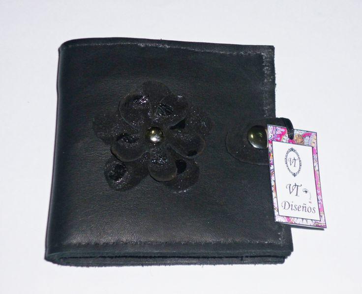 Billetera de cuero color negro, con detalle de flor en cuero negro con brillo.