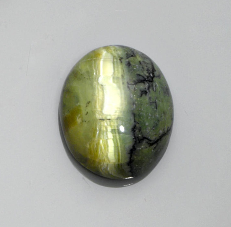 Brazilian Cat's Eye Opal Cabochon  Brazil   To our knowledge no more that 80 kilos of this rare variety of cat's eye opal have been mined in the last 30 years. This particularly rare green opal is found in veins in dark brown volcanic rock and the color is due to iron content. The present oval cabochon features a seam of chatoyant orange opal in its green matrix. This is the only location in which this particular type of opal can be found.