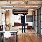 Love this - the bed can be hoisted up and out of the way, by a counterbalancing 300 lb weight.  When not in use as the headboard, the large redwood slab folds down to become a desk.