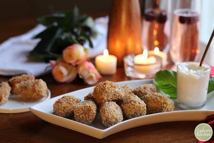 Platter of vegan fried artichoke hearts with lemon garlic aioli. Candles & roses in background.