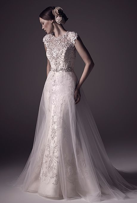 Amar� Couture Bridal. From the bateau neckline to the elegant fit-and-flare bodice, Mila is adorned with hand-beaded lace appliqu�s. The silhouette is delicately shrouded by a detachable A-line tulle skirt, and an illusion back complete with a zip closure is disguised by ornate beading.
