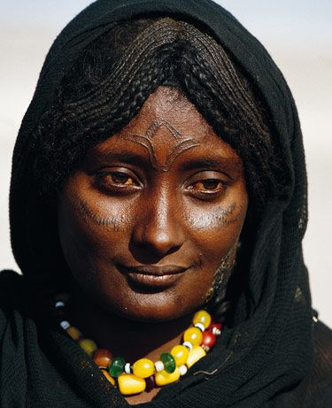 "Afar Woman, Ethiopia ""Facial scarification serves both as a means of establishing tribal identity and a way to enhance physical beauty. The curved pattern of cow horns on the forehead of this serene woman indicates that she is from a cattle-herding family and comes from a gentle and more fertile part of Afar country than the harsh Danakil Depression."""