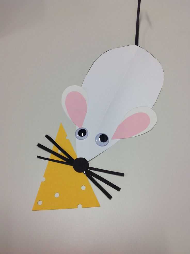 Mouse craft. Cut a large teardrop shape from white card. Fold in half. Stick on two teadrop shaped ears. Cut out three strips of black card and stick on tip of nose for whiskers. Punch a black dot for a nose and stick on to cover centre of whiskers. For the tail, cut a strip of black cardboard and use scissors or a strong fingernail to curl slightly. Attach on underside. Stick on eyes. For cheese, cut triangle of yellow card and use hold punch to make holes.
