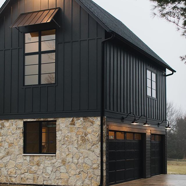 Black Moder Farmhouse With Black Board And Batten Siding Flagstone Stone Accent And Black Garage Doors Exterior House Colors House Exterior Black Garage Doors