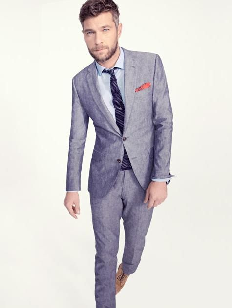 Brown shoes and orange pocket square on a gray suit