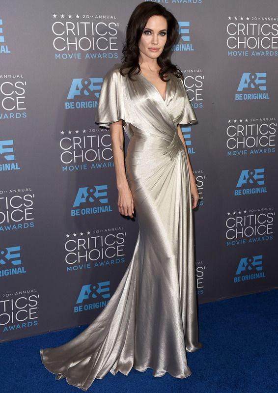 Una deslumbrante Angelina Jolie acudió a la gala con un vestido de seda plateada drapeado con mangas acampanadas de Versace.  Critics' Choice Movie Awards 2015