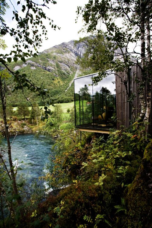 Glass apartment tucked away next to a river