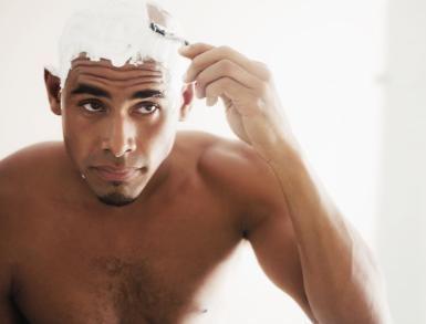 A black man shaving his head - Dylan Ellis/Photodisc/Getty Images