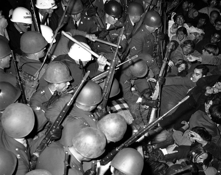 """soldiers-of-war: """" USA. Washington. October 21, 1967. U.S. troops use their rifles in an encounter with antiwar demonstrators outside the Pentagon. Photograph: AP """" You can see men in the background wearing helmets that read """"US Marshals""""."""