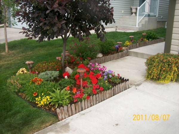 This small front yard garden bed has a nicely arranged mix of annuals and perennials. This wooden edging is affordable and easy to install  for do-it-yourselfers. Picture compliments of DIY homeowner.