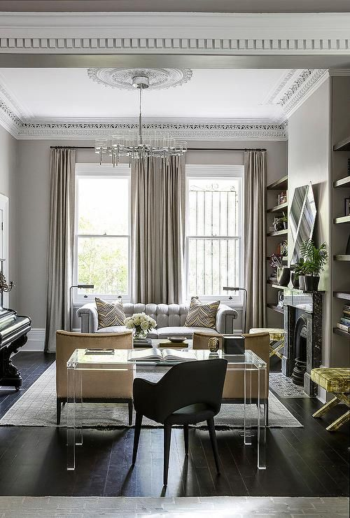 Yellow and grey living room features a gray chesterfield sofa adorned with yellow and black pillows placed in front of windows dressed in taupe curtains facing a pair of yellow velvet chairs with silver nailhead trim atop a gray rug alongside a lucite desk paired with a black task chair.