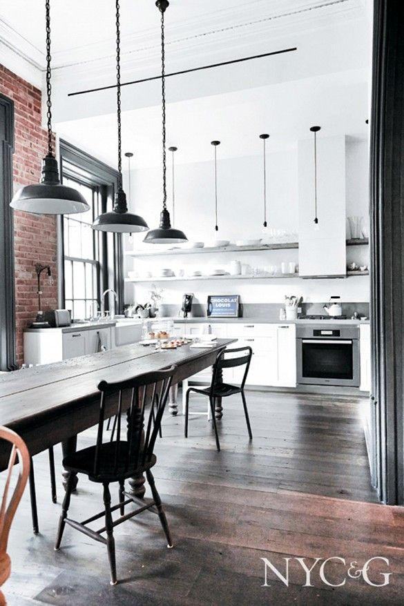 White kitchen with industrial dining space and light fixtures and exposed brick wall