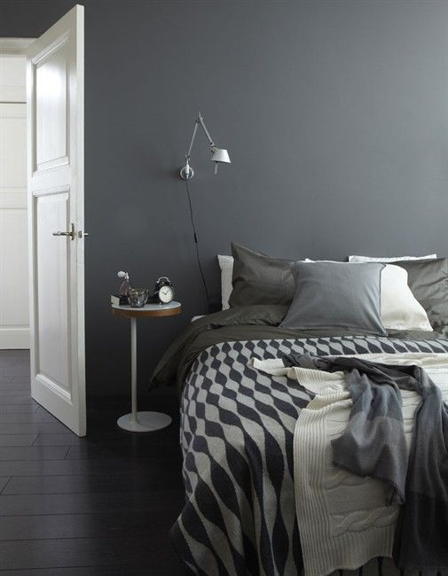 Grey and white end room with bedside lamp on wall