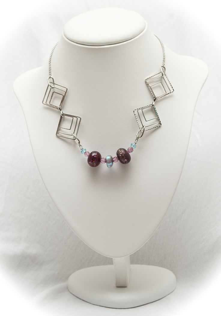 on a silver toned chain, a necklace of deep pink art glass beads with dichroic glass highlights,