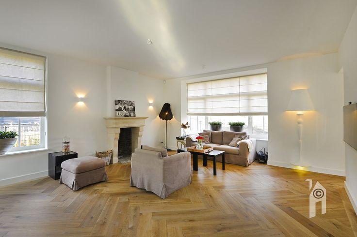 Grote lichte woonkamer met hoge raampartijen.