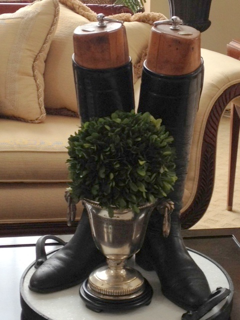 Vignette of riding boots and boxwood in trophy cup from the polohouse blog