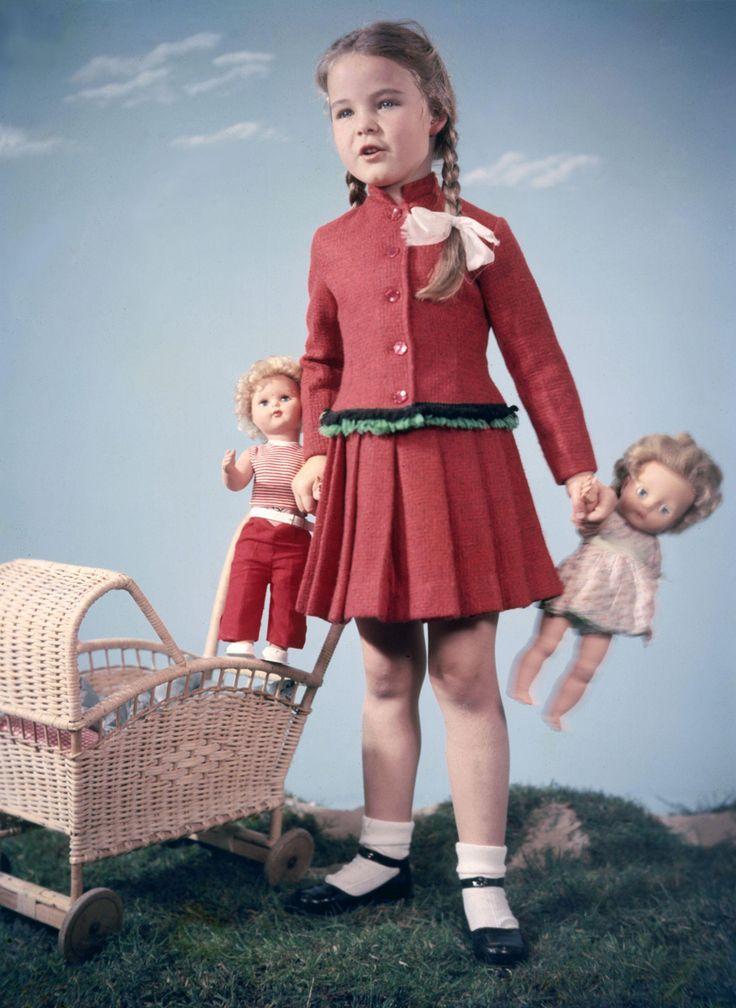 Meisje in een rood pakje met plooirok, witte sokjes en zwarte lakschoenen en het haar in vlechten, poseert met in elke hand een pop in een studio-decor met rieten poppenwagen. 1961-1962. Maker: fotograaf: Walter Blum