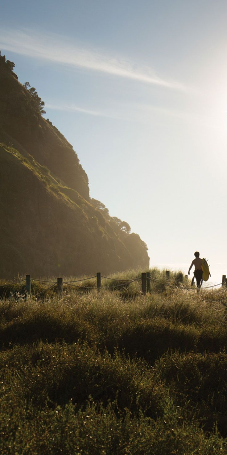 Heading out for a surf at Piha Beach in Auckland - by Craig Parry