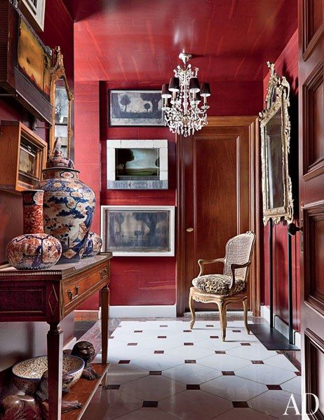 In the foyer, paintings by Alexander Mihaylovich are interspersed with antique mirrors; the ceiling and walls are sheathed in a wallpaper by Maya Romanoff | archdigest.com