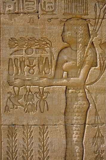 Carving of a woman (mourner?) making an offering of various foods to the deceased. Often found nearby would be a scene of the deceased seated at a table heaped with foodstuffs. Both are powerful magic spells to provide the deceased with plenty of food in the afterlife