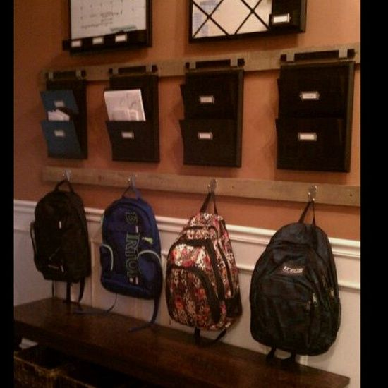 """""""Welcome home"""" organization station--places for backpacks, homework to do, slips to be signed, and a calendar with upcoming events."""