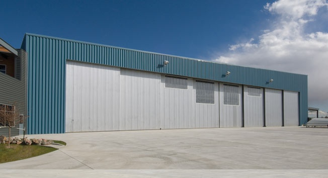 """Our """"Smart Rail"""" HWB840, eight section side and bi-parting bottom rolling hangar door. This system maximizes the usable space within the hangar facility. Most popular with fixed base operations. The door opening size for this project was 175'-0"""" wide by 28-0"""" high."""