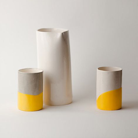 """""""These striking dip cups, by up in the air somewhere, are glazed in either a light grey or white glaze and then hand dipped in yellow rubber."""" via http://www.iainclaridge.co.uk"""