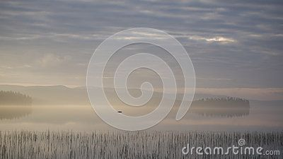 A sunrise above a lake, the fog lifts, fishing adventure in Boden, Sweden.