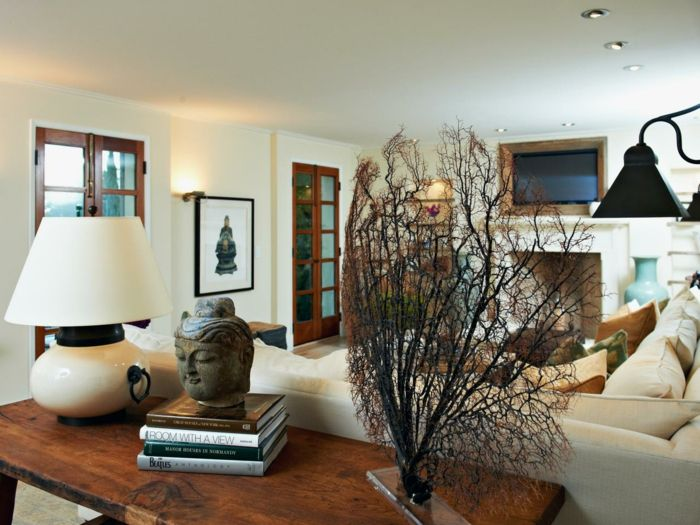 bouddha zen, deco salon zen, table en bois avec des livres et tete de bouddha, luminaire sur la table avec abat-jour en blanc et base en ivoire, décoration de table avec des branches d'arbres, luminaire mural en métal noir